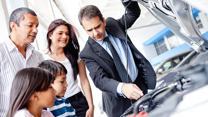 Familia recibiendo indicaciones de un especialista en el mantenimiento de vehículos