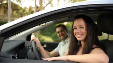 Una joven sonriente conduciendo un automóvil asegurado