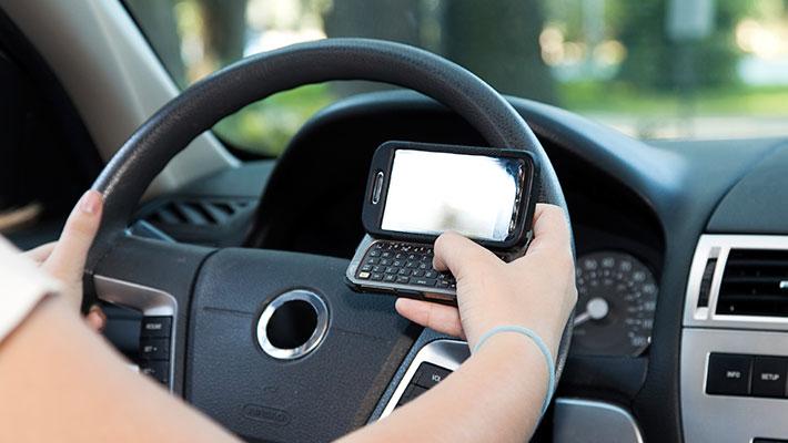conductor imprudente haciendo uso de su teléfono celular mientras conduce su vehículo
