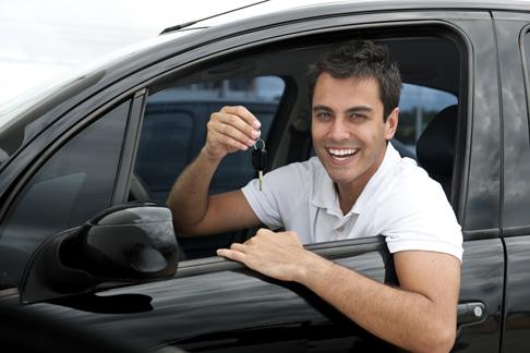 Conductor feliz sosteniendo la llave de su vehículo al obtener su seguro de auto.