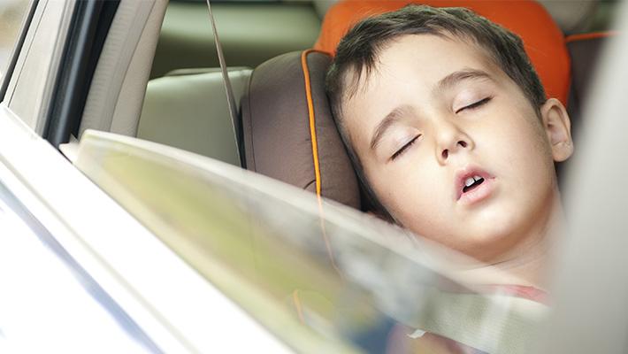 Niño durmiendo dentro de un vehículo